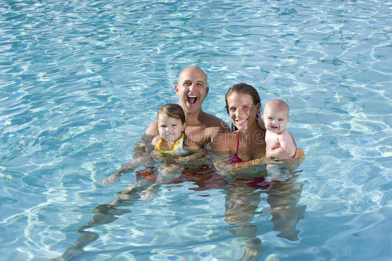 Portrait of young family smiling in swimming pool stock image