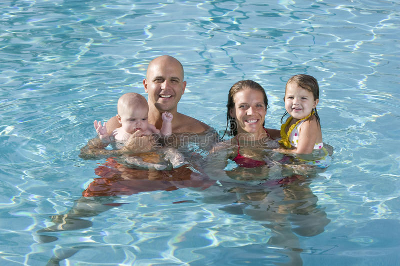 Portrait of young family smiling in swimming pool royalty free stock photos