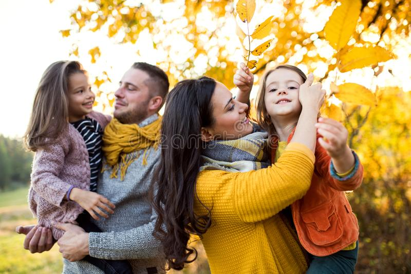 A portrait of young family with two small children in autumn nature. royalty free stock image