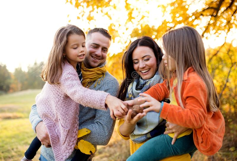 A portrait of young family with two small children in autumn nature. royalty free stock images