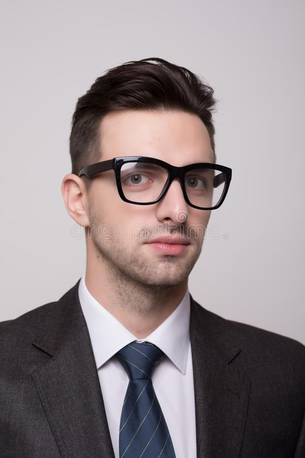 Portrait of a young and fashion businessman with nerd glasses on gray royalty free stock images