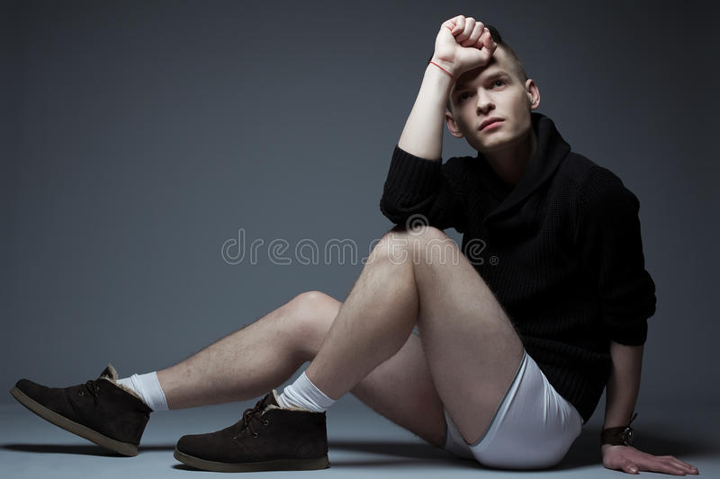 Portrait of young fashionable man in trendy clothes. Portrait of a young fashionable man in trendy clothes and underwear sitting over gray background. Hipster stock images
