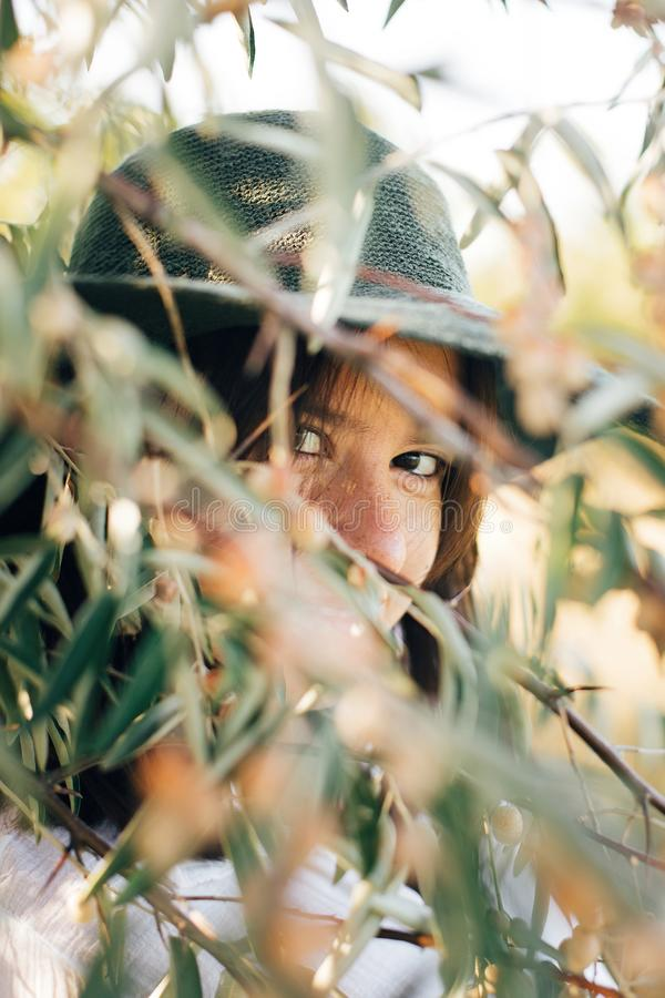 Portrait of young fashionable woman with modern earrings posing in  green olive branches in soft evening light, stylish boho girl. In hat relaxing on tropical royalty free stock images