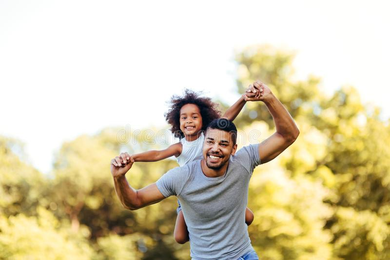 Portrait of young father carrying his daughter on his back royalty free stock images