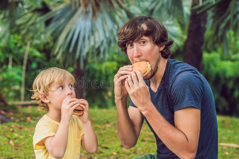 Portrait of a young father and his son enjoying a hamburger in a stock photos