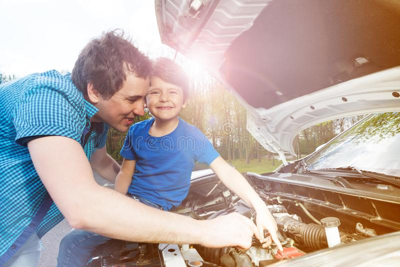 Young father teaching his little son repairing car stock images