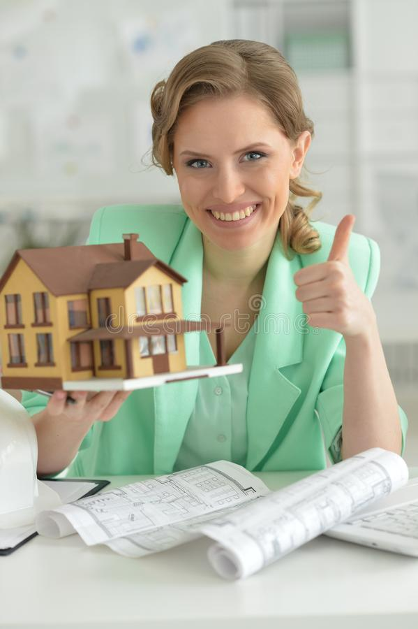 Portrait of young female architect holding model of house stock image