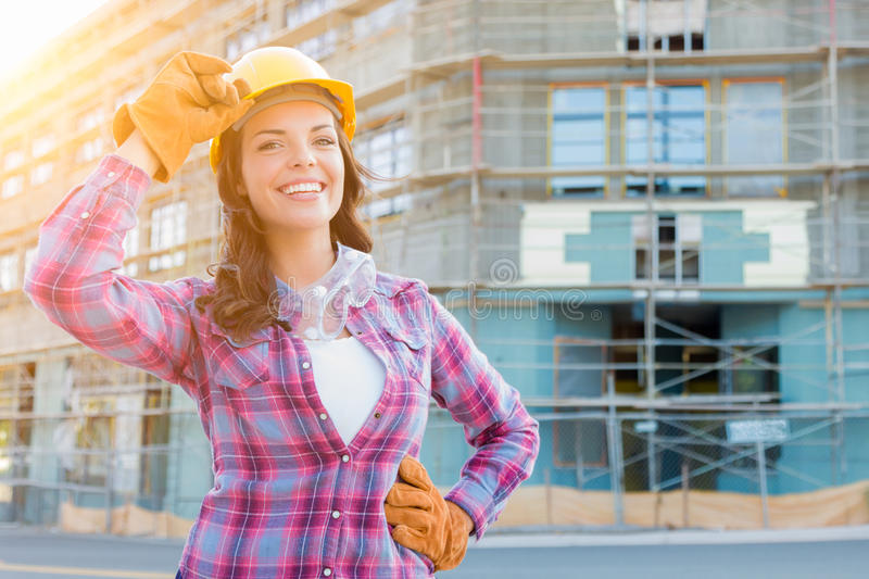 Portrait of Young Female Construction Worker Wearing Gloves, Hard Hat and Protective Goggles at Construction Site. royalty free stock photography