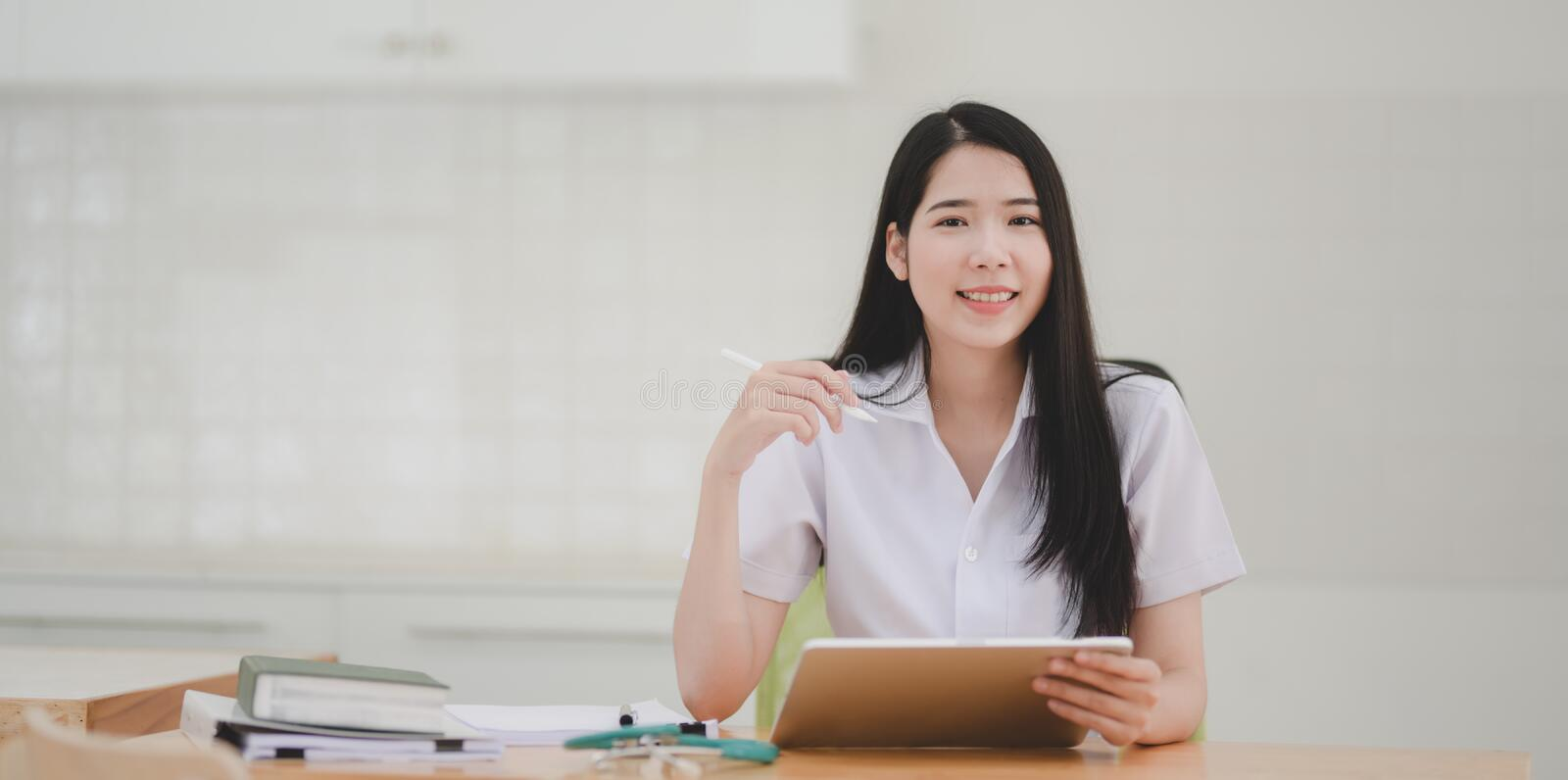 Portrait of young female doctor examining the patient chart and smiling to the camera royalty free stock images