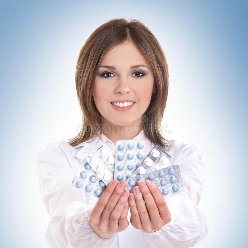 Portrait of a young female doctor holding pills