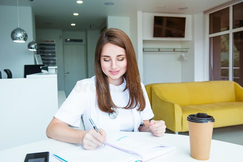 Portrait of young female doctor making notes in notebook while sitting behind the table with phone and coffee inside of medical royalty free stock photos