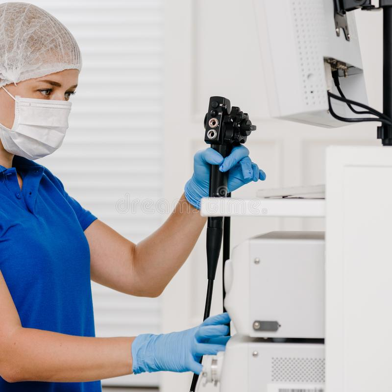 Doctor with ultrasound machine. Portrait of young female doctor operating ultrasound machine royalty free stock image