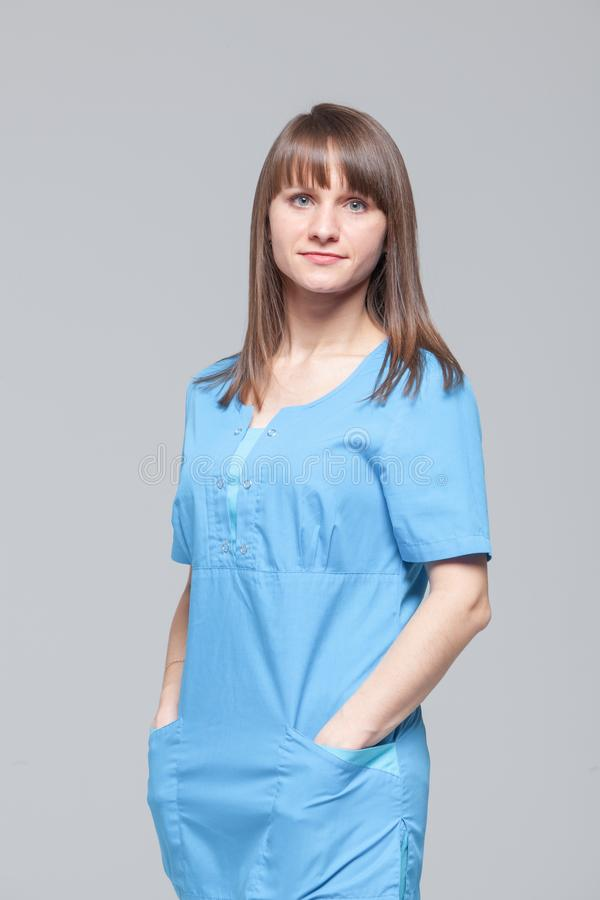 Portrait of young female doctor standing in blue uniform royalty free stock images