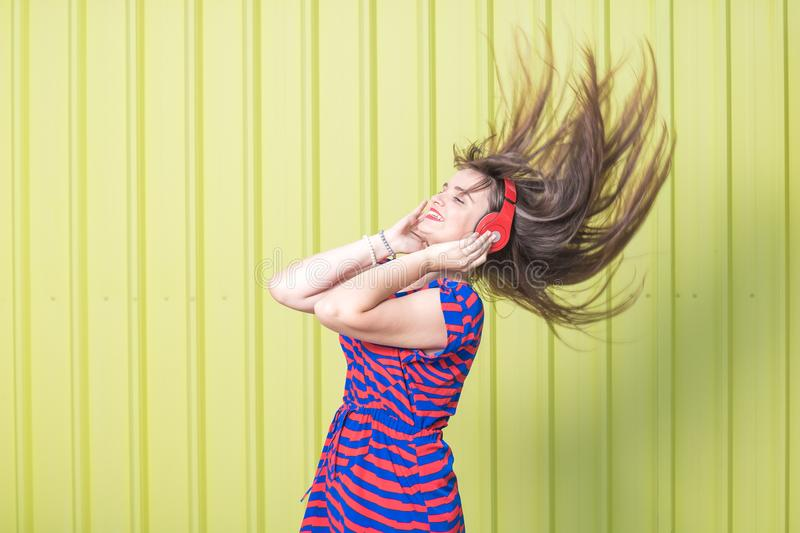 Beautiful woman in stripped dress enjoying her favorite song on yellow background. royalty free stock image
