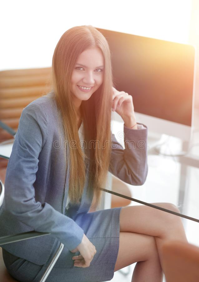 Female office employee sitting at a Desk. Portrait of young female office employee sitting at a Desk royalty free stock photography