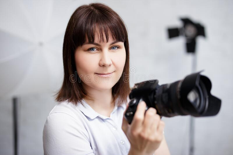 Portrait of young female photographer posing with camera in her studio stock photo