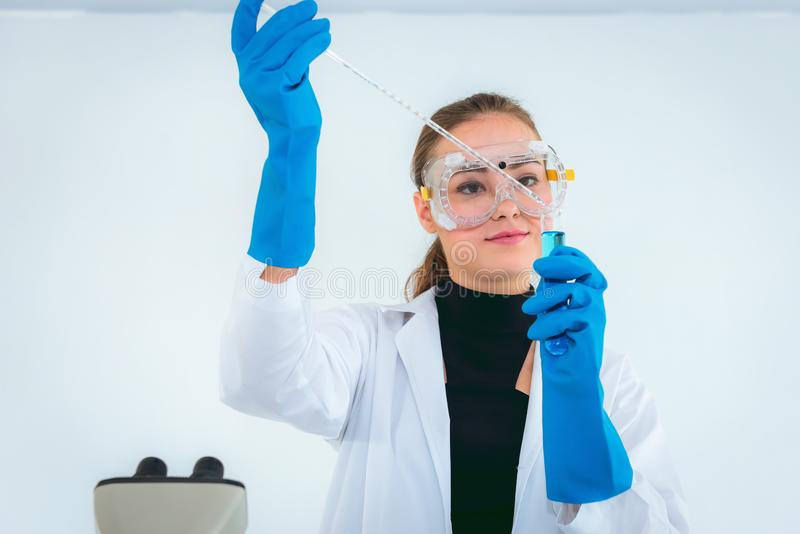 Portrait of young female research scientist is mixing chemical and analyzing result through microscope in research laboratory room stock image