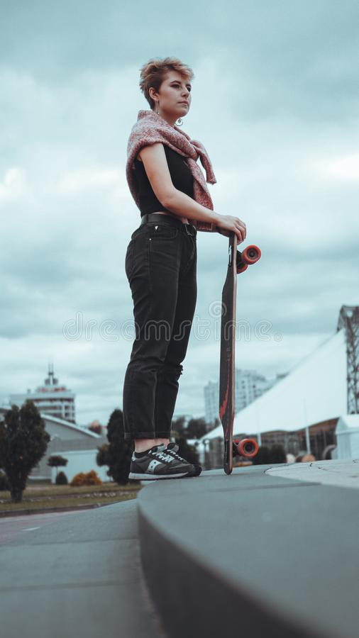 Portrait of young female skateboarder holding her skateboard. Woman with skating board at skate park looking at camera outdoors stock images