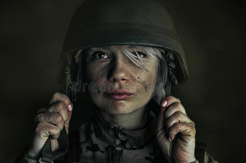 Portrait of young female soldier. Death is not so terrifying as a fight with it. Close up portrait of young female soldier. Woman in military uniform on the war stock photography