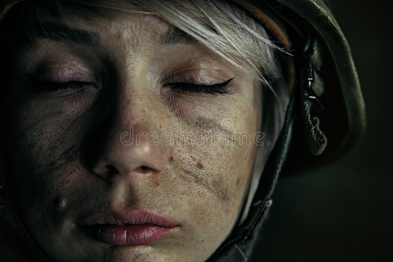 Portrait of young female soldier. No tears and no fear anymore. Close up portrait of young female soldier. Woman in military uniform on the war. Depressed and stock photography