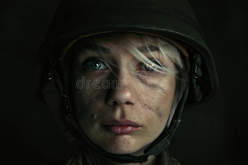 Portrait of young female soldier. Only one chance to be alive. Close up portrait of young female soldier. Woman in military uniform on the war. Depressed and royalty free stock photo