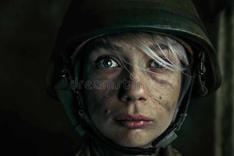 Portrait of young female soldier. Only one chance to be alive. Close up portrait of young female soldier. Woman in military uniform on the war. Depressed and royalty free stock photos