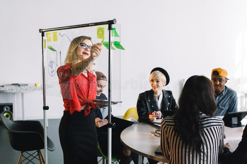 Portrait of young female team leader of talented freelances organizing work of members motivates and inspire them to. Make researching, standing near glass stock photos