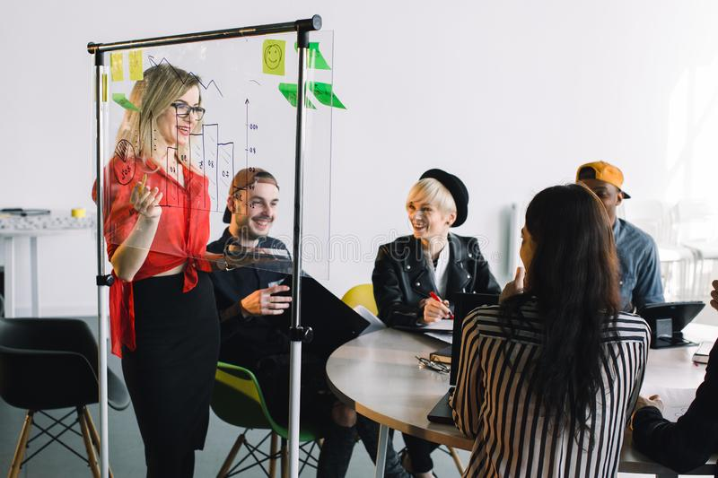 Portrait of young female team leader of talented freelances organizing work of members motivates and inspire them to. Make researching, standing near glass royalty free stock image