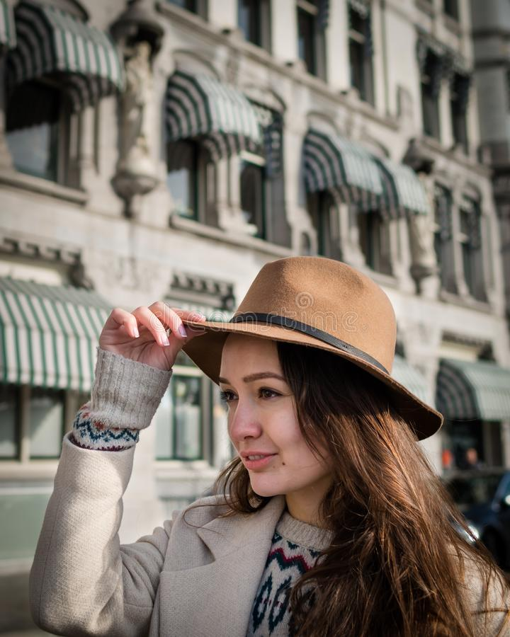 Portrait of a young female tourist with elegant clothes exploring the city. Trendy woman traveler with smile looking on buildings and touring old town royalty free stock photos