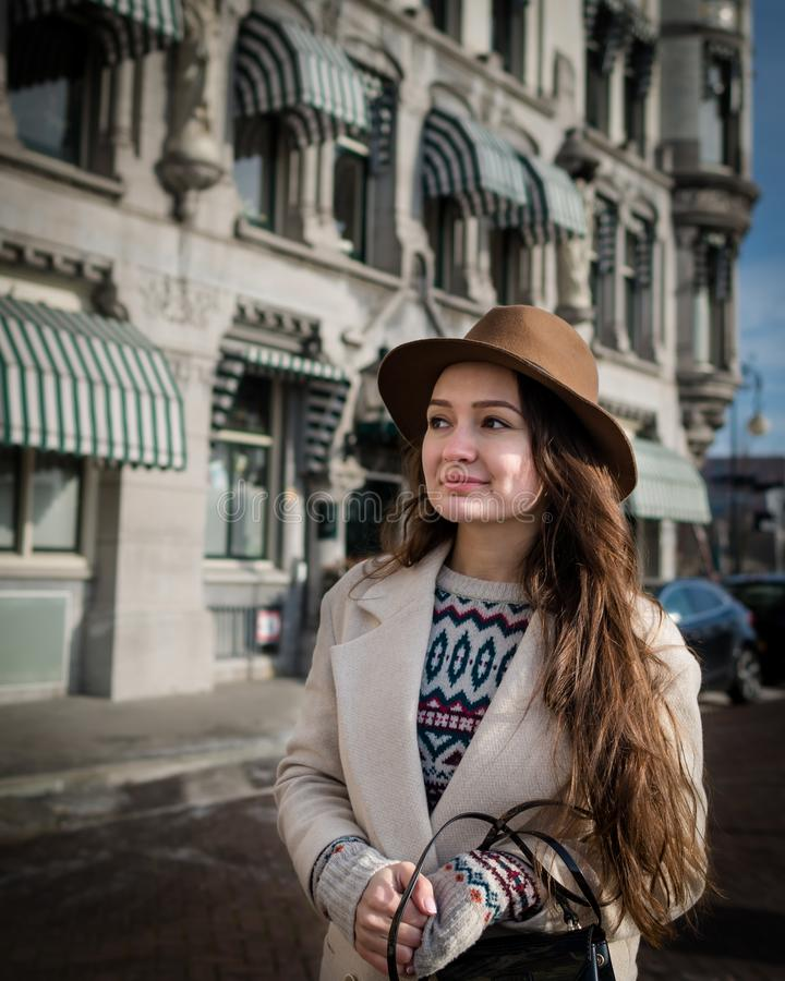 Portrait of a young female tourist. With elegant clothes walking in the city. Trendy woman traveler with smile looking on buildings and touring old town stock photo