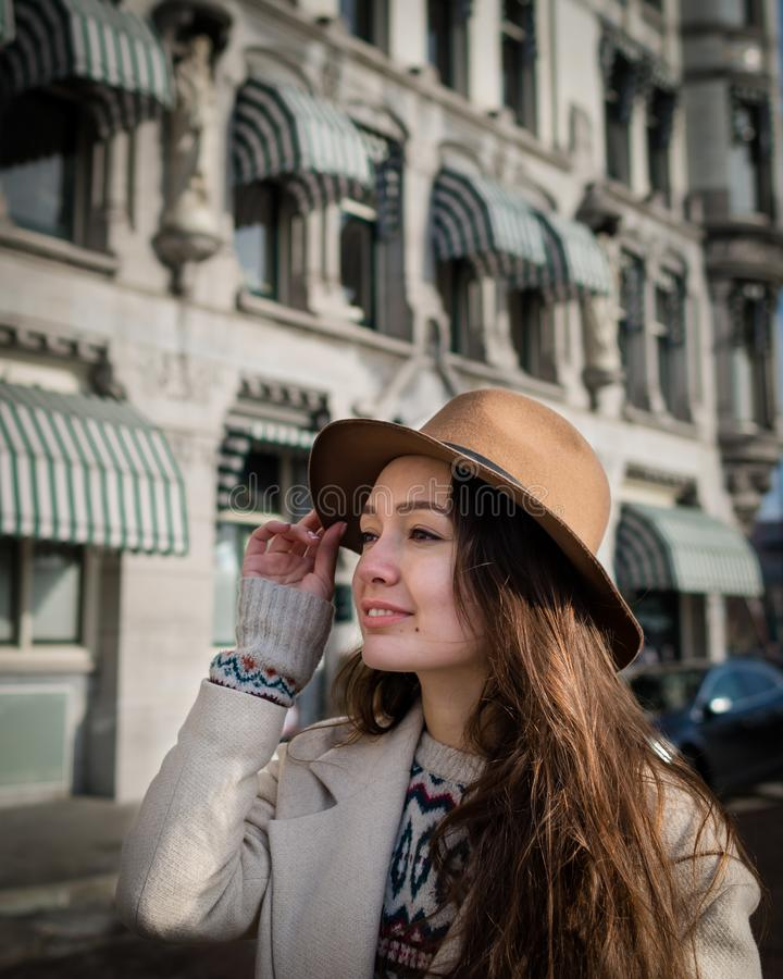 Portrait of a young female tourist with elegant hat. And coat exploring the city. Trendy woman traveler with smile touring old town. Beautiful girl walks in stock photo