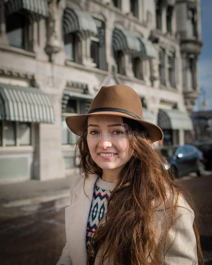 Portrait of a young female tourist with elegant hat. And coat exploring the city. Trendy woman traveler with smile touring old town. Beautiful girl walks in royalty free stock photo