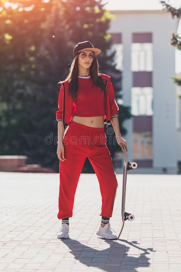 Portrait of young female wearing black hat, red clothing skateboarder holding her skateboard. Woman with skating board. Portrait of young female wearing stock photography