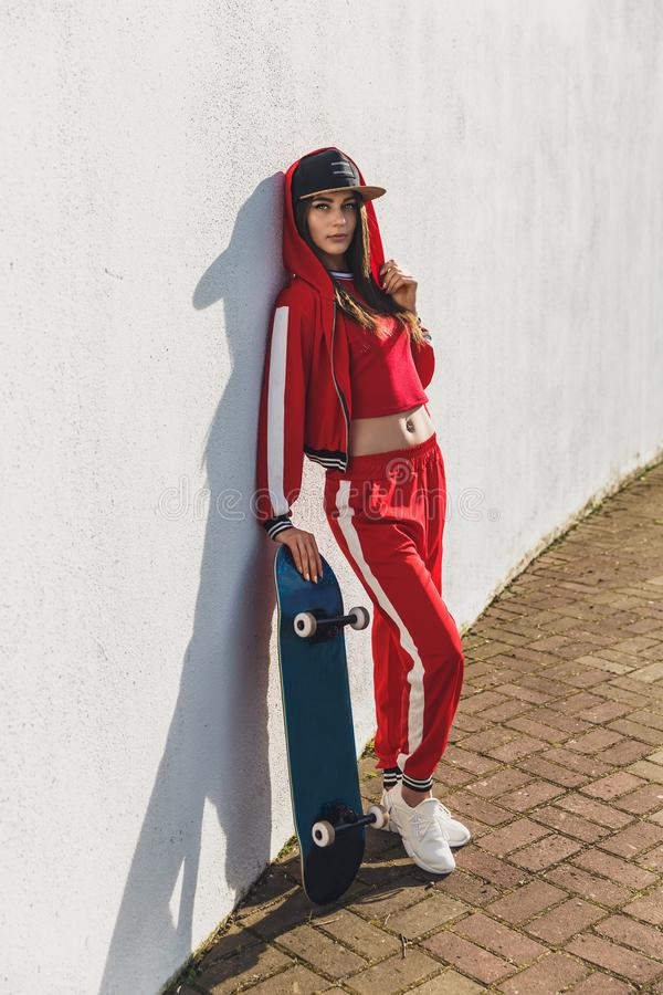 Portrait of young female wearing black hat, red clothing skateboarder holding her skateboard. Woman with skating board. Portrait of young female wearing stock photo