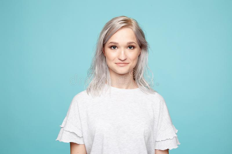 Portrait of young female in the white t-shurt in the blue background. royalty free stock photos