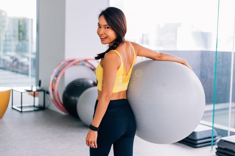 Portrait of young fit Asian woman holding exercise swiss ball and smiling at camera. Lively female fitness model image stock images