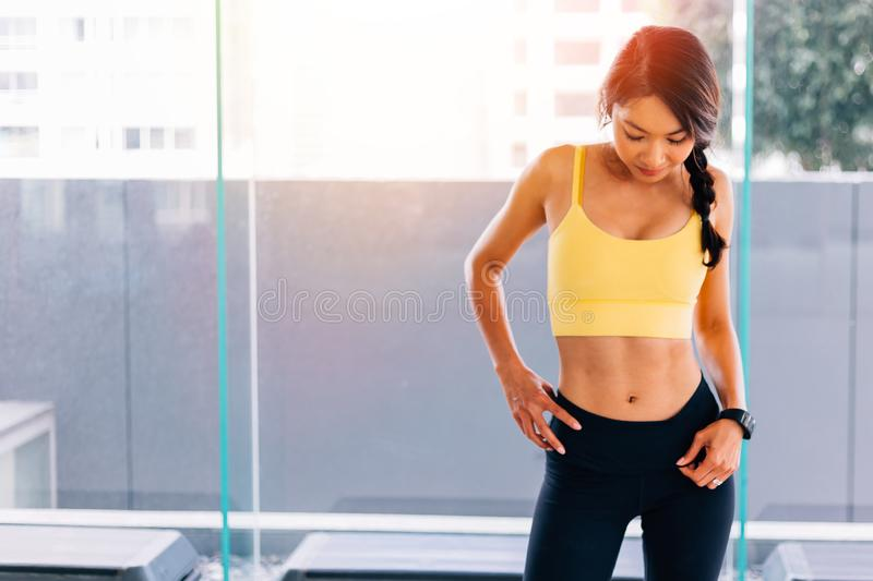 Portrait of young fit Asian woman standing in gym, hands on hips pose. Fitness female model image stock image