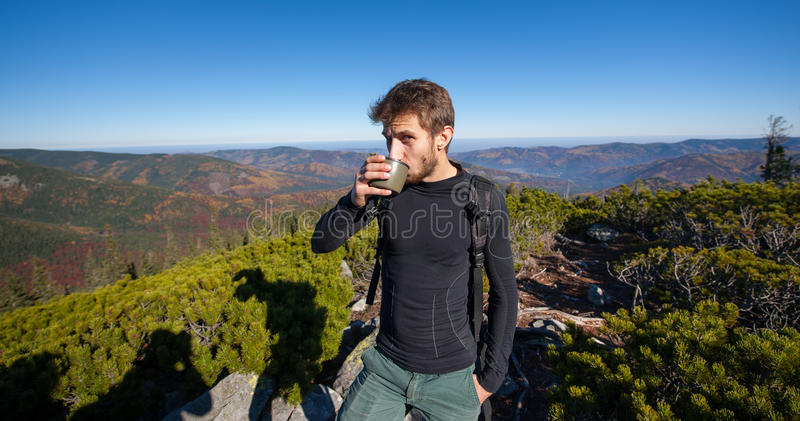 Portrait of young fit male hiker drinking tea royalty free stock photography