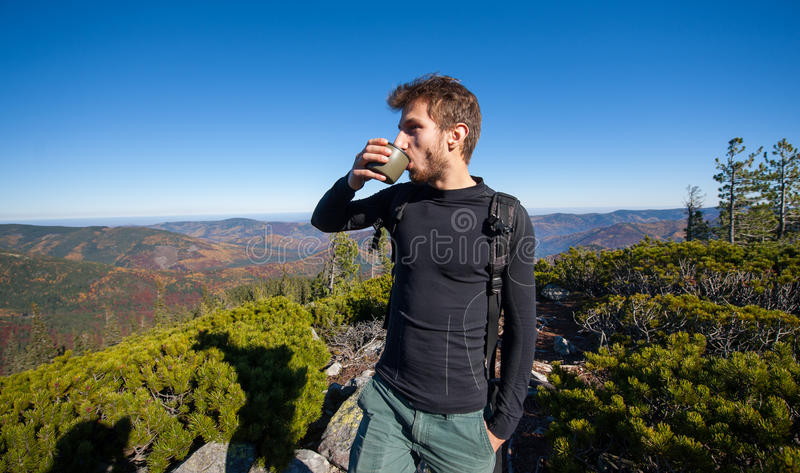 Portrait of young fit male hiker drinking tea stock image