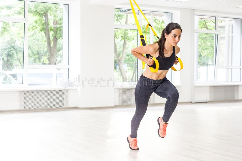 Portrait of young fit woman in black sportswear training arms with trx fitness straps in the gym doing push ups train upper body. Chest shoulders pecs triceps stock images