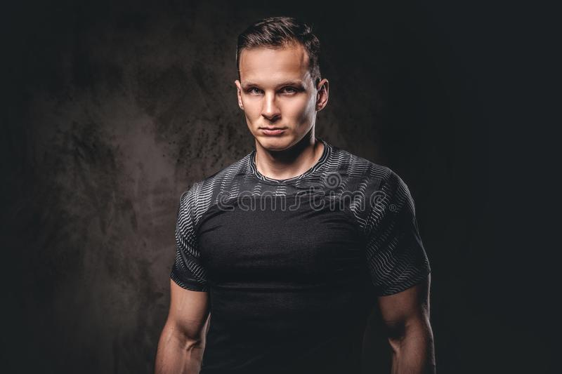 Portrait of a young fitness man wearing sportswear looking at camera on dark background. stock photography