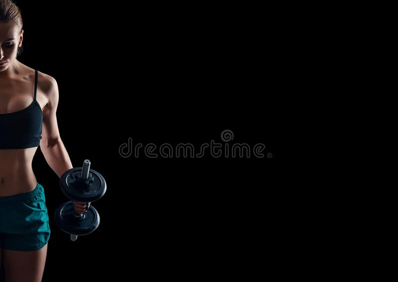 Portrait of a young fitness woman in sportswear doing workout with dumbbells on black background. Tanned athletic girl. A gre royalty free stock photo