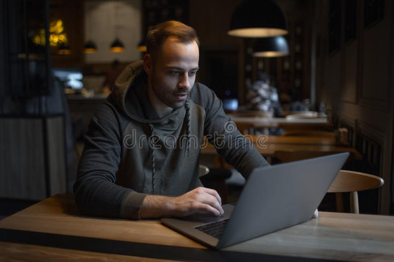 Portrait of young freelancer, man who using laptop in cafe royalty free stock images