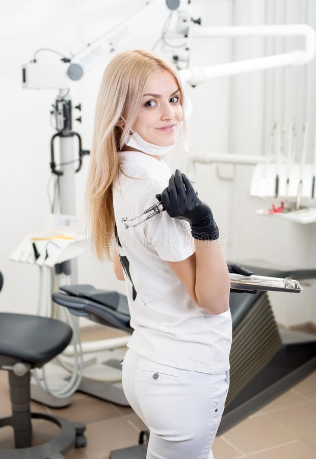 Portrait of young attractive female dentist holding dental tool at the modern dental office royalty free stock photography