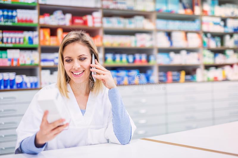 Portrait of a young friendly female pharmacist with smartphone. royalty free stock image
