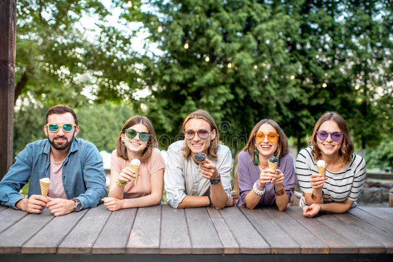 Friends with ice cream in the cafe. Portrait of a young friends sitting together with ice cream outdoors in the park royalty free stock image