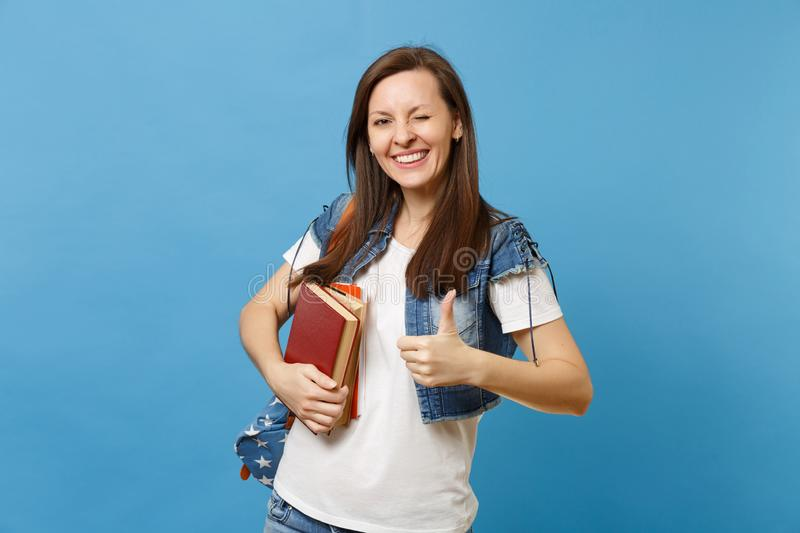 Portrait of young funny cute woman student in denim clothes with backpack blinking showing thumb up, hold school books stock photo