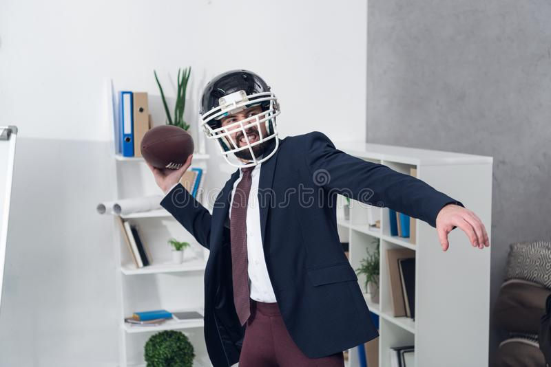 Portrait of young furious businessman. In helmet playing rugby in office stock image