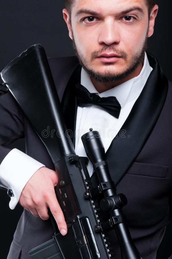 Portrait of young gangster holding armed rifle stock photo