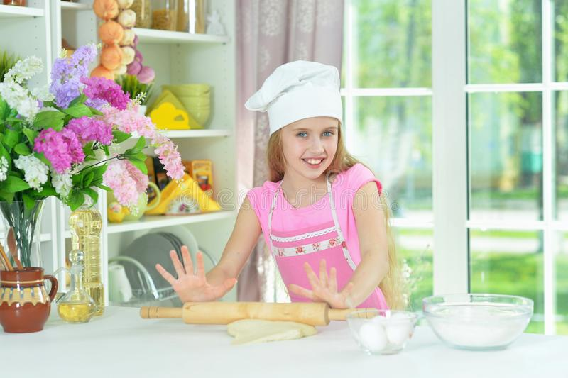 Portrait of young girl baking in the kitchen. Young beautiful girl baking and posing in the kitchen at home royalty free stock photo